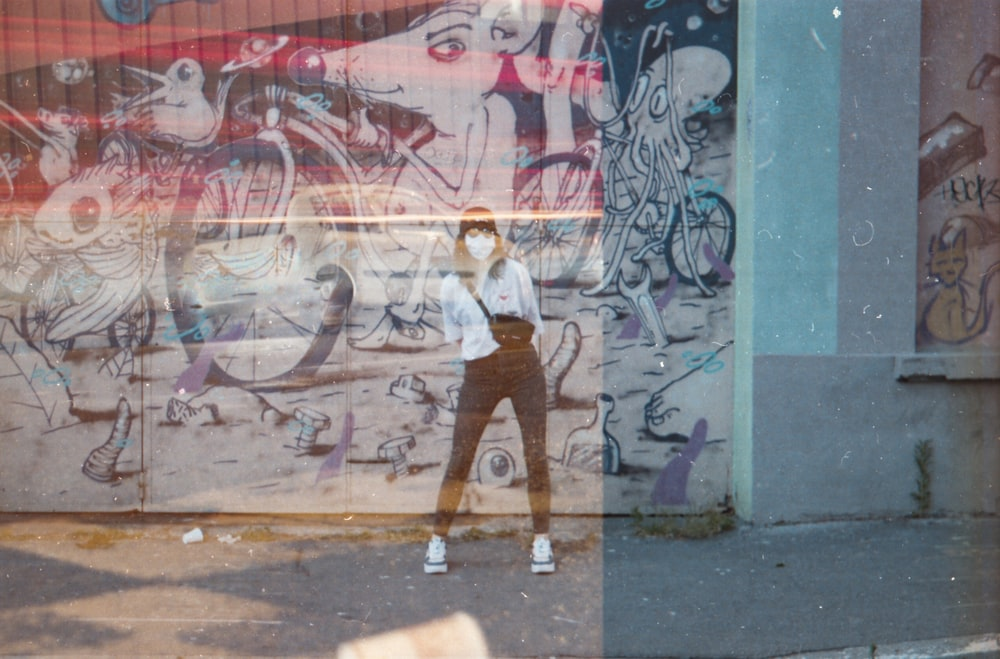 woman in white shirt and brown pants standing beside graffiti wall during daytime