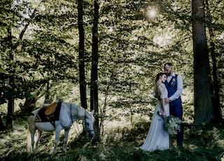 woman in white dress standing beside man in blue dress shirt