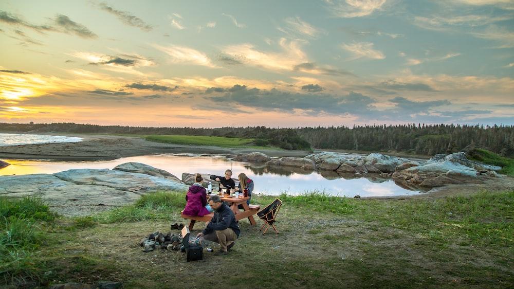 people sitting on camping chairs near lake during daytime