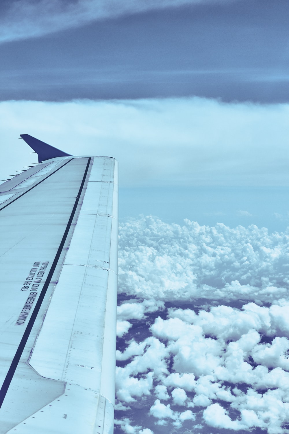 white airplane wing over white clouds during daytime