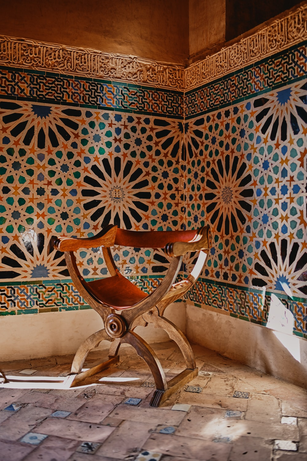 brown wooden chair beside white and blue floral wall