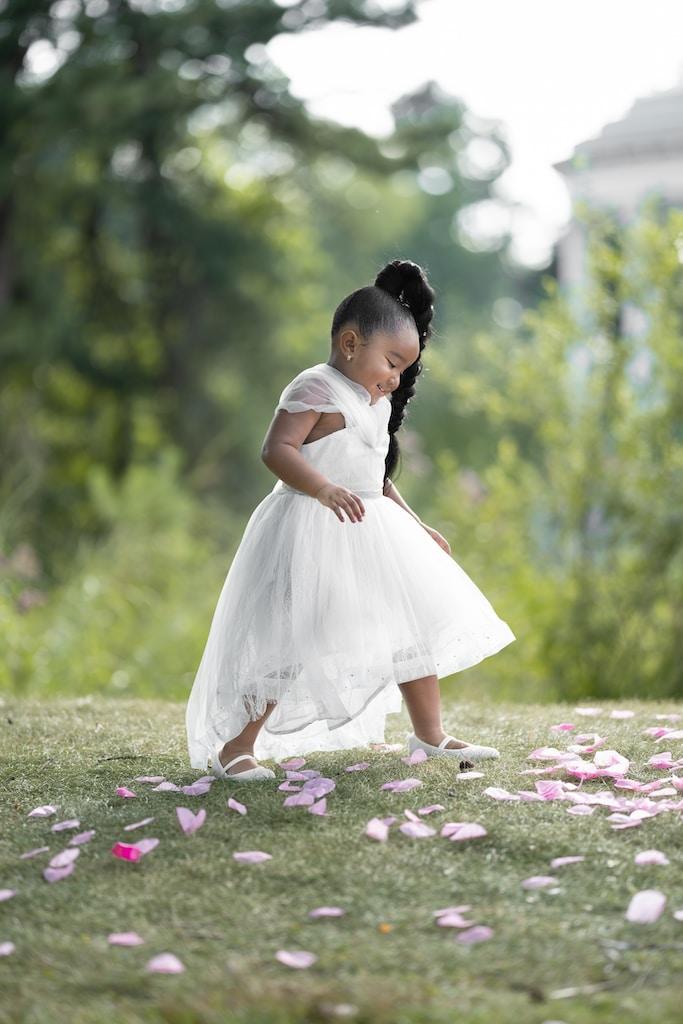 girl in white dress standing on flower field during daytime