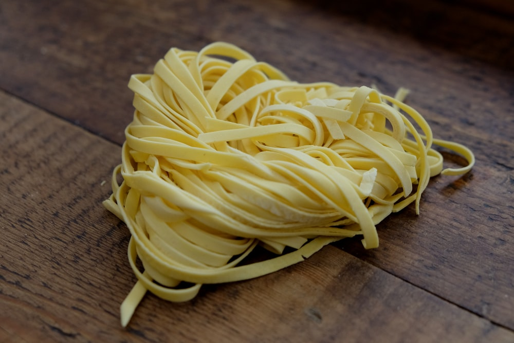 yellow pasta on brown wooden table
