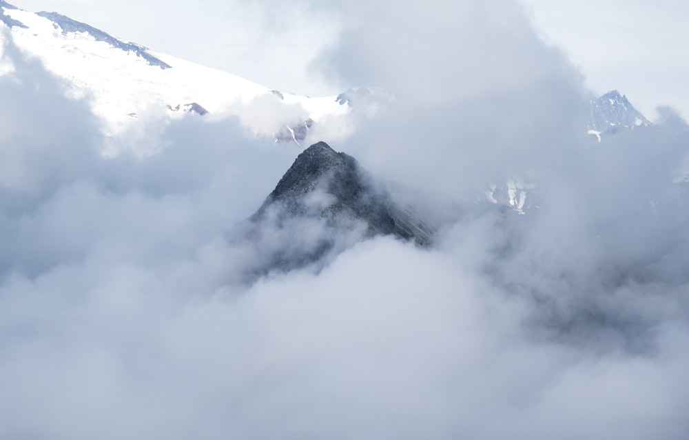 white clouds over snow covered mountain