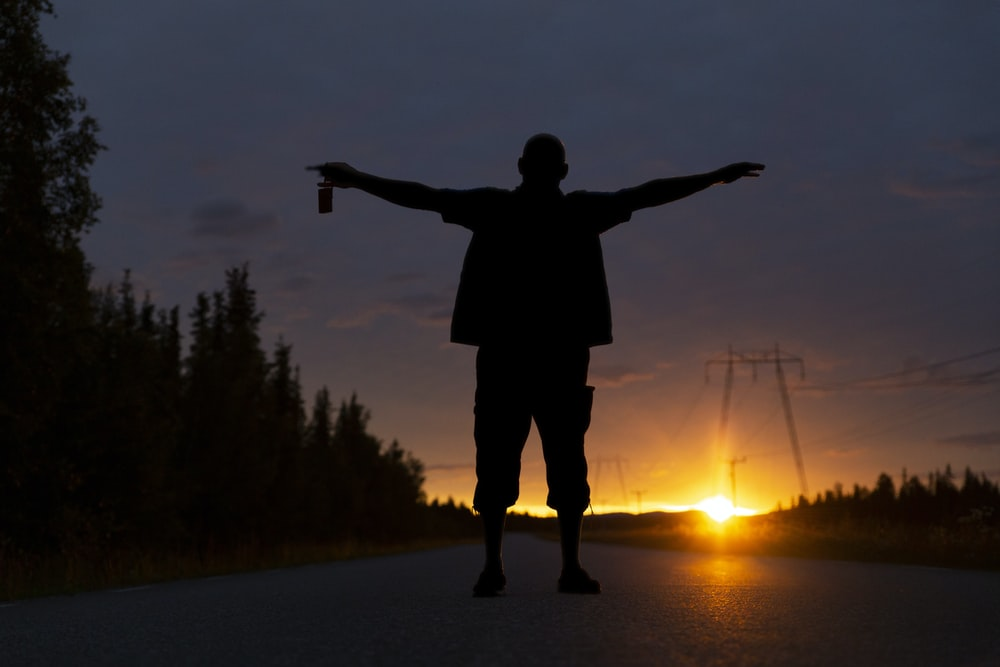 silhouette of man standing on road during sunset