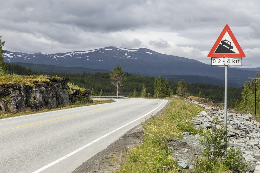 steep asphalt road and grass field with mountain