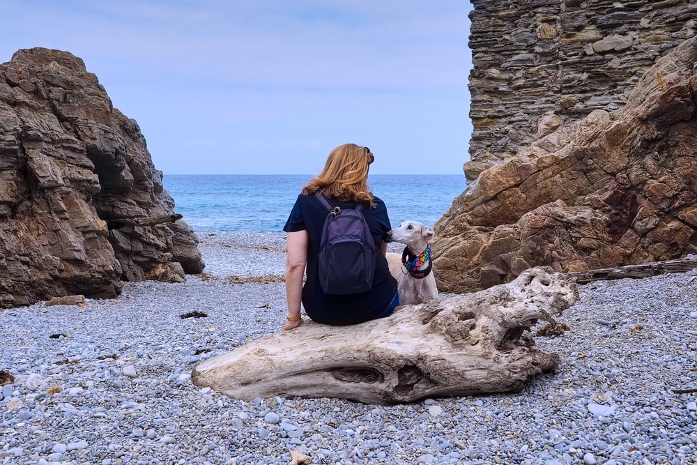 woman in black t-shirt sitting on brown rock formation near sea during daytime