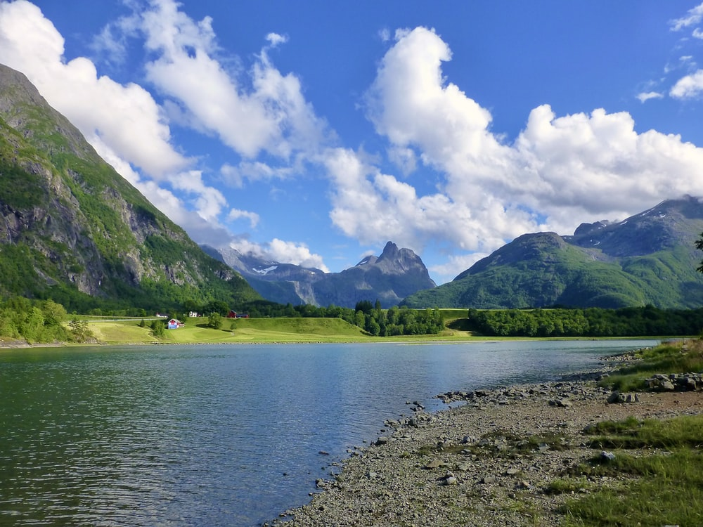 green mountains beside lake under blue sky and white clouds during daytime