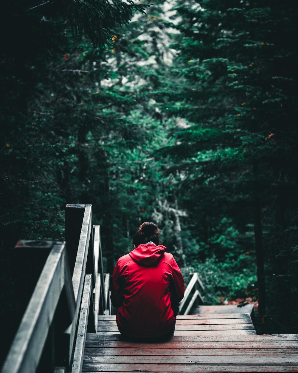 person in red hoodie sitting on brown wooden bridge