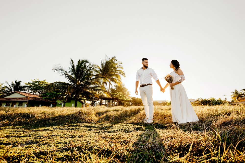 man and woman in white wedding dress walking on brown grass field during daytime