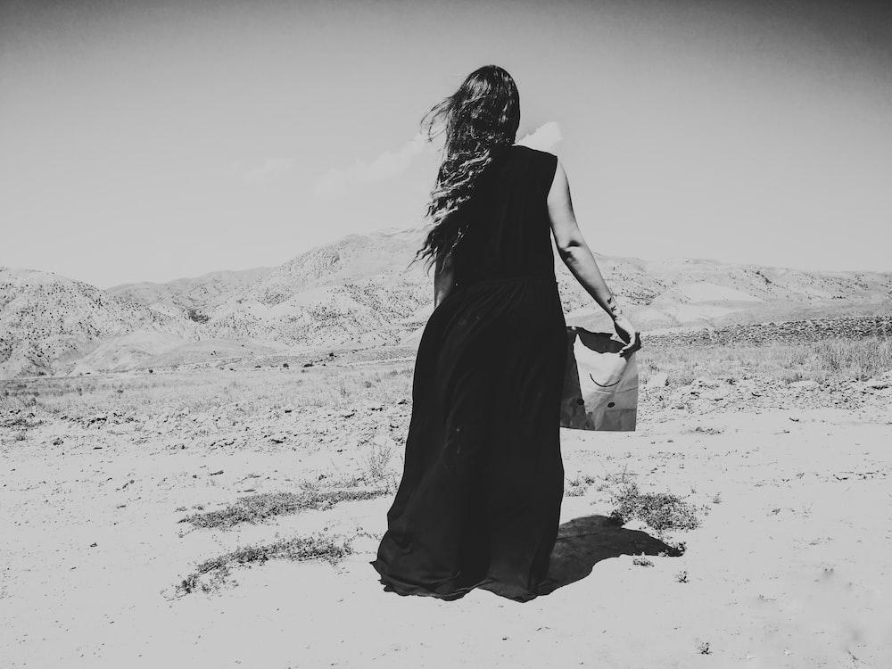 woman in black dress walking on sand