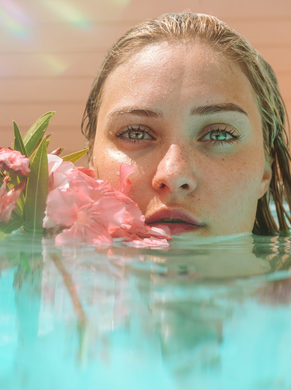 woman in water with pink flower petals