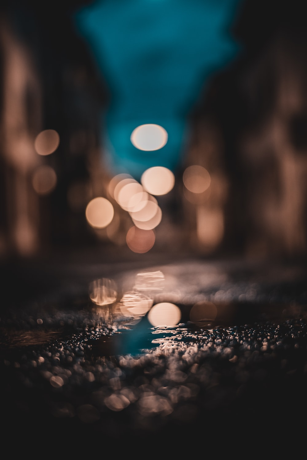bokeh photography of water droplets on ground
