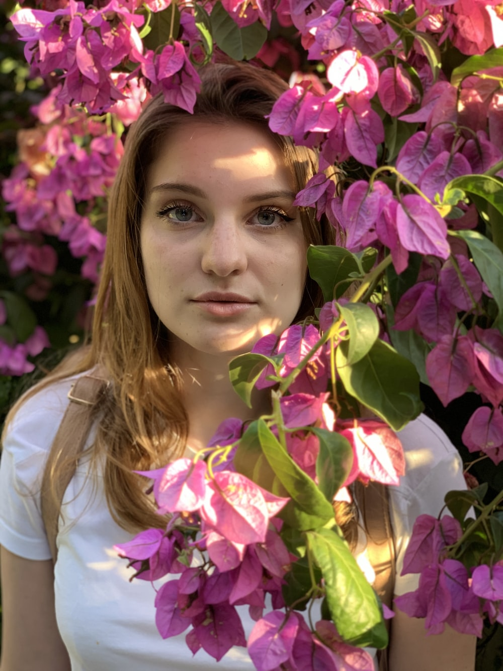 woman in white shirt standing beside pink flowers
