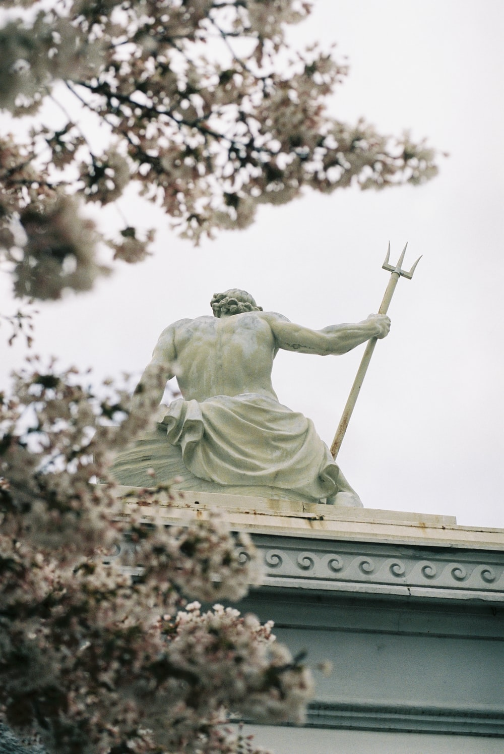 angel holding stick statue during daytime