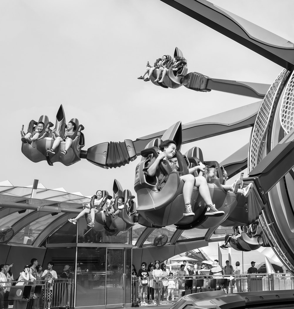 grayscale photo of people riding on a roller coaster