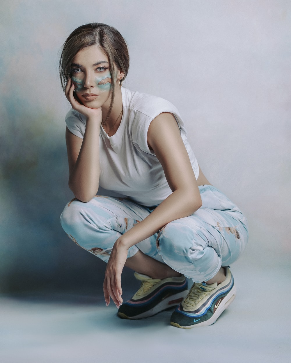 woman in white tank top and blue and white pants sitting on floor