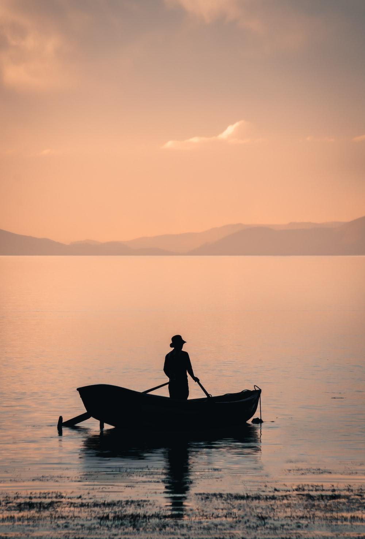 man in boat on lake during daytime