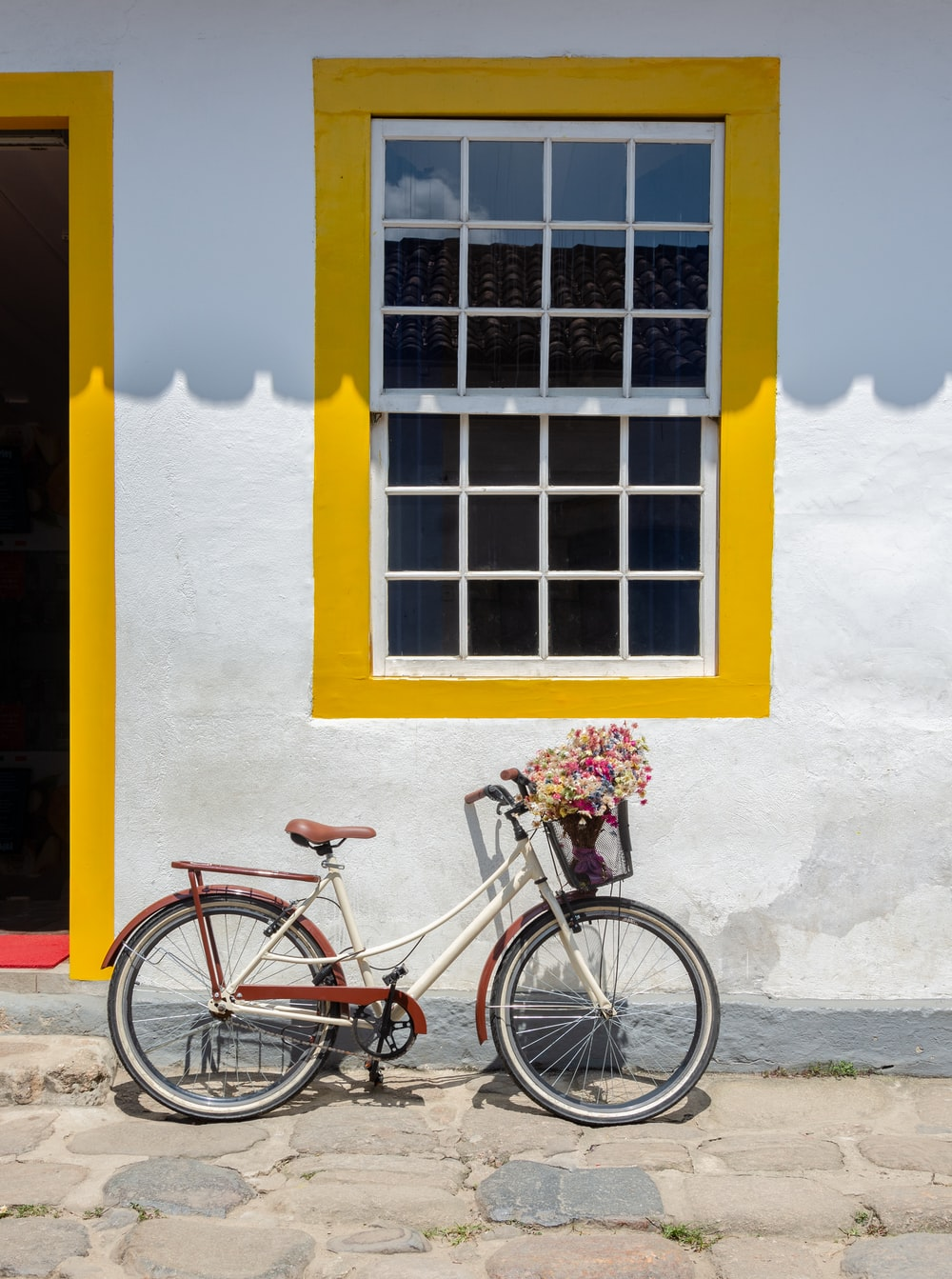 blue city bike parked beside yellow painted wall