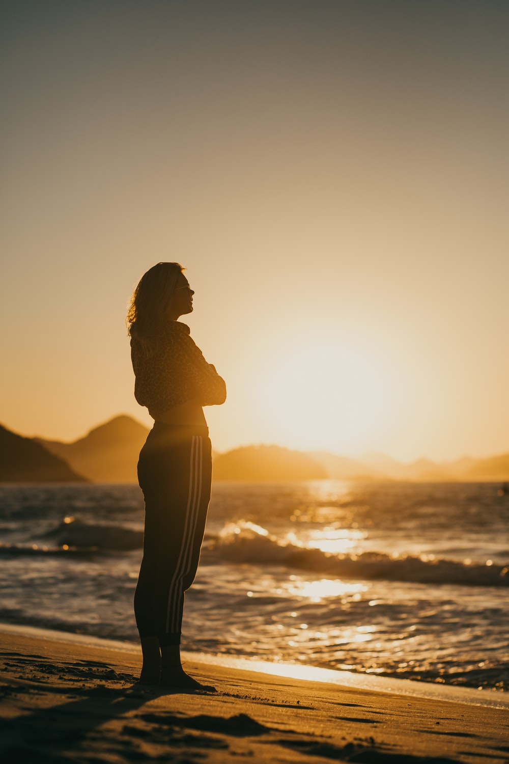 silhouette of woman standing on seashore during sunset