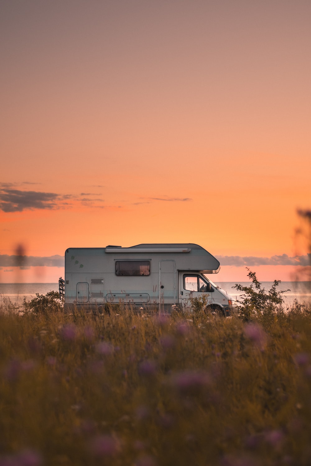 white and gray rv on green grass field during sunset