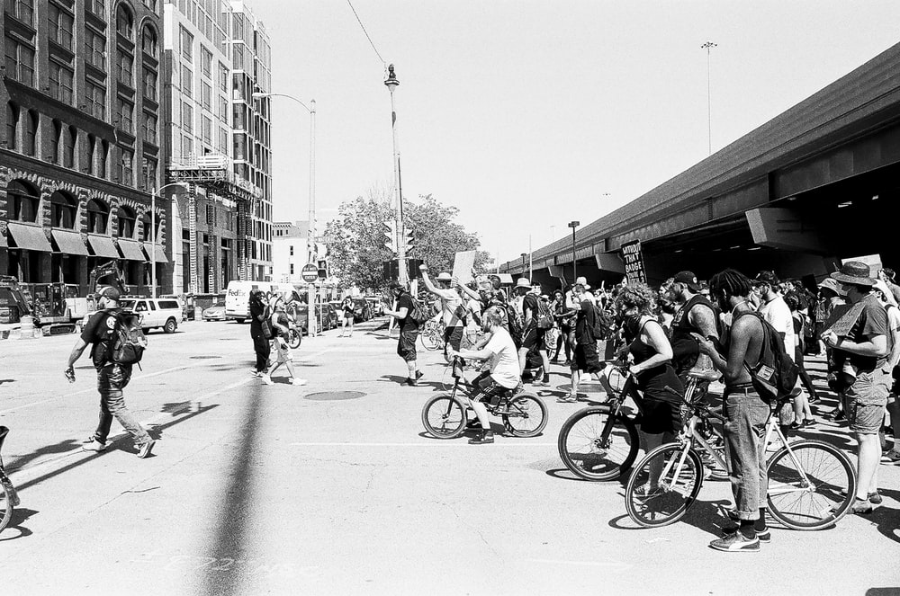 people riding bicycles on street in grayscale photography