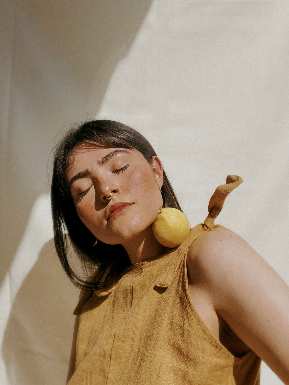 woman in yellow sleeveless dress holding yellow fruit