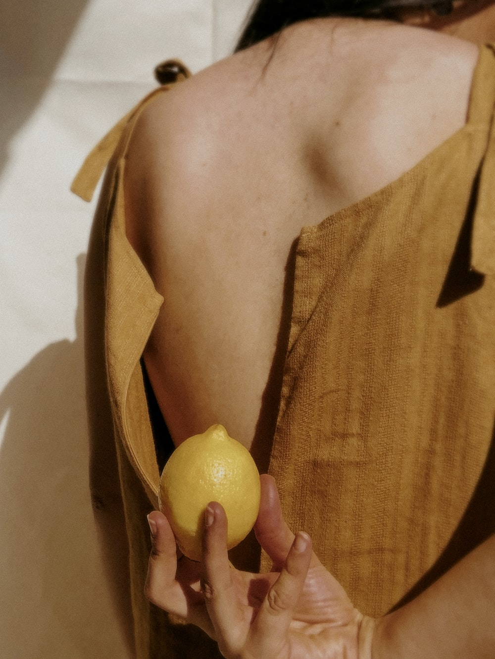 woman holding yellow lemon fruit