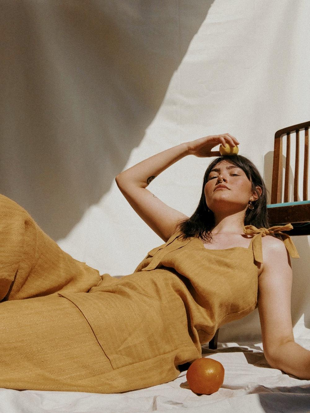 woman in brown sleeveless dress lying on bed