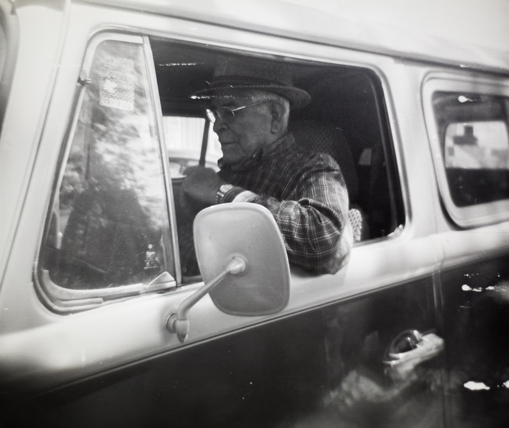 man in black and white plaid dress shirt driving car