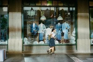 woman in blue dress walking on sidewalk during daytime