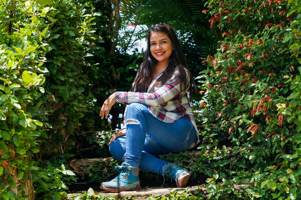 woman in blue denim jeans sitting on brown dried leaves