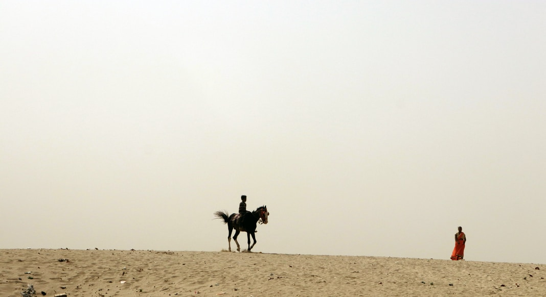 2 people riding horses on brown sand during daytime