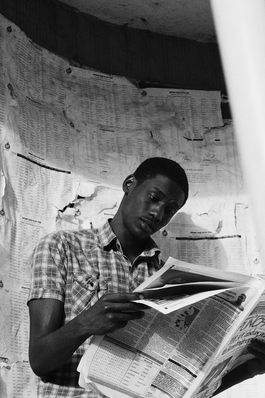 man in plaid shirt reading book