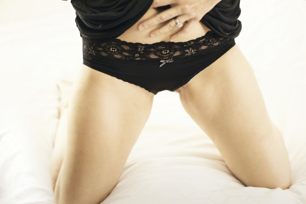 woman in black lace panty lying on bed