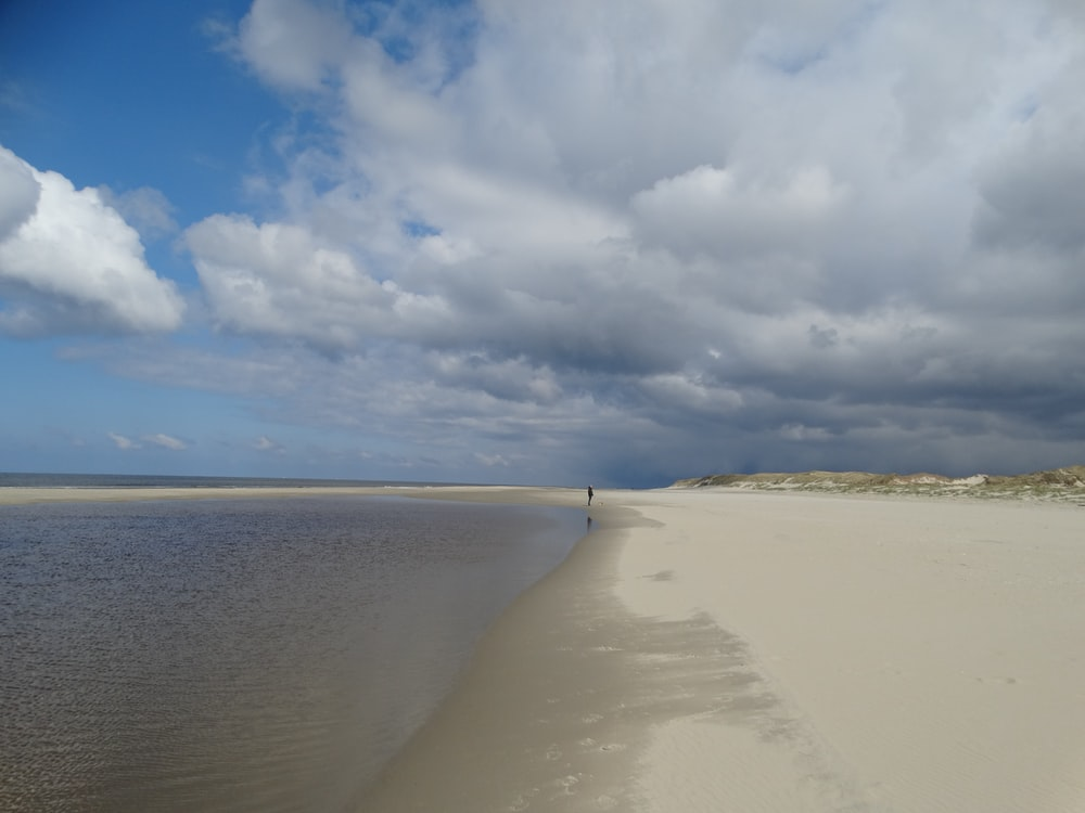 white sand beach under blue sky and white clouds during daytime