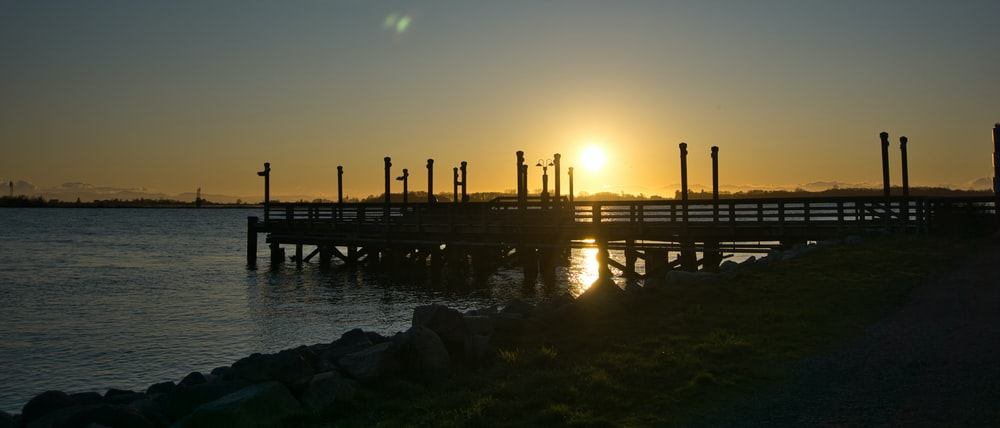 silhouette of wooden dock on sea during sunset