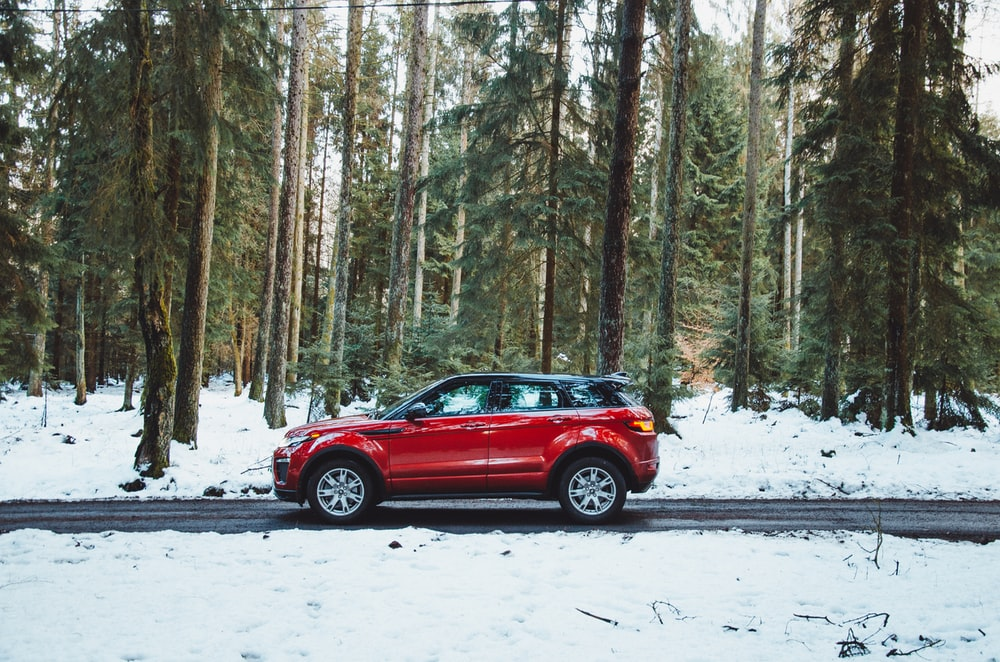 red suv on snow covered road during daytime
