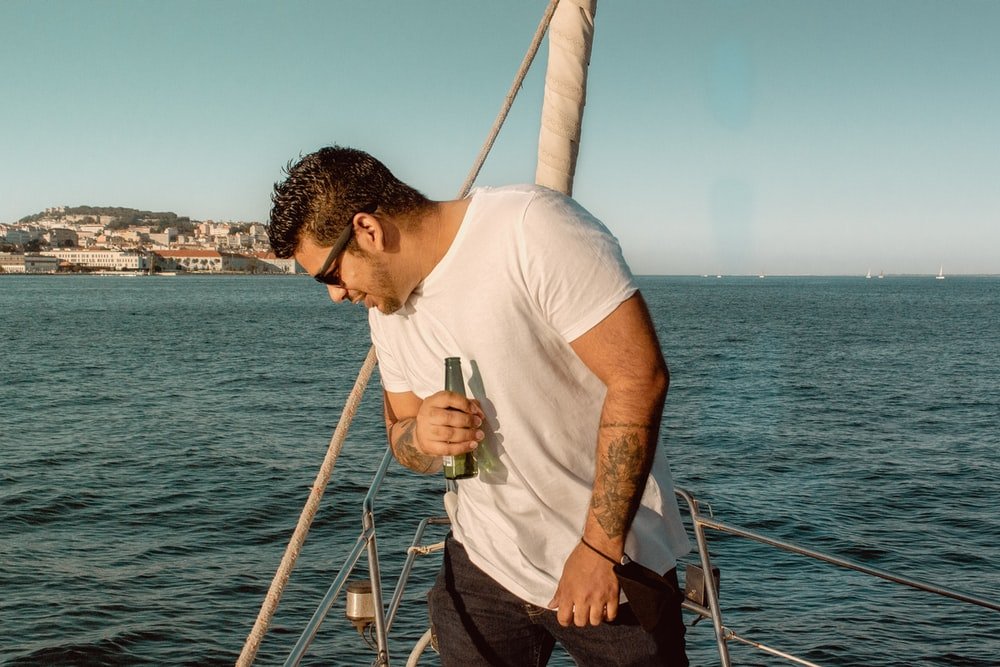 man in white crew neck t-shirt and black pants holding a glass of drink