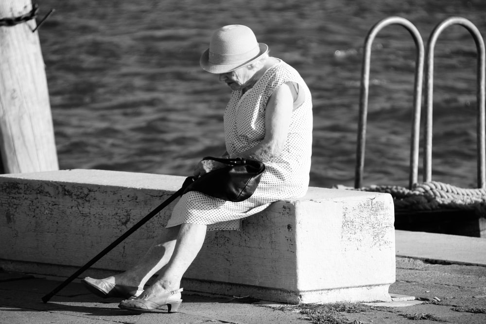woman in white long sleeve shirt and white pants sitting on concrete bench