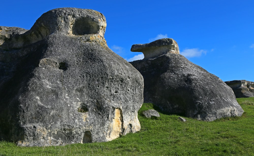 gray rock formation on green grass field under blue sky during daytime