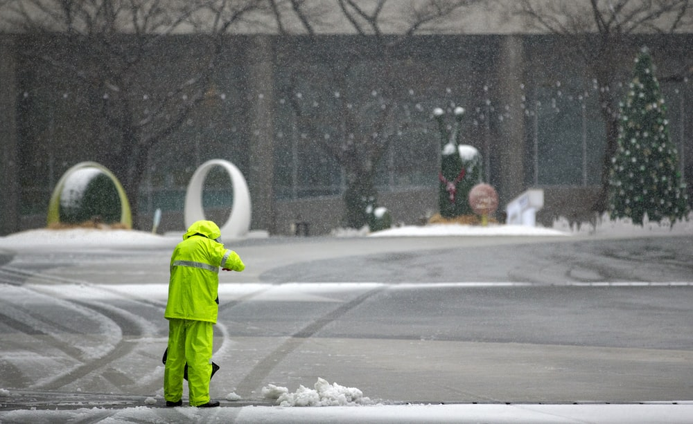 person in green jacket walking on road during daytime