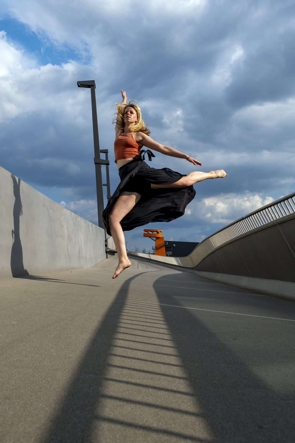 woman in black tank top and black pants jumping on gray concrete road during daytime