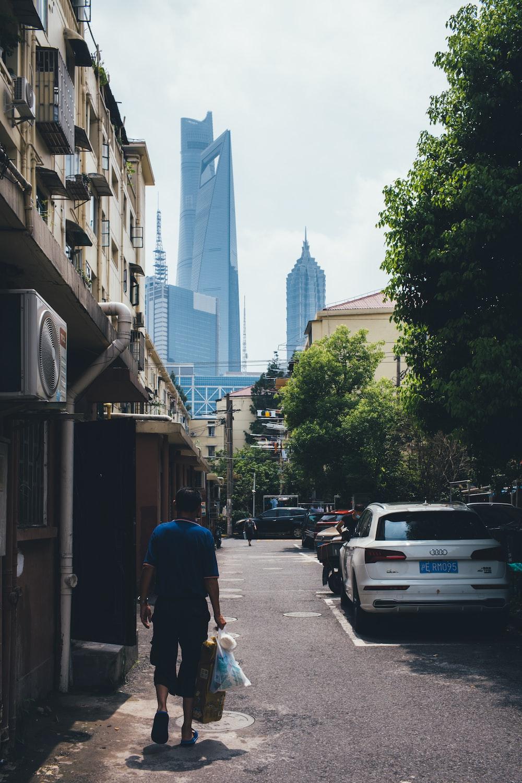 man in blue t-shirt walking on sidewalk during daytime