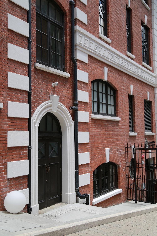 brown brick building with black wooden door