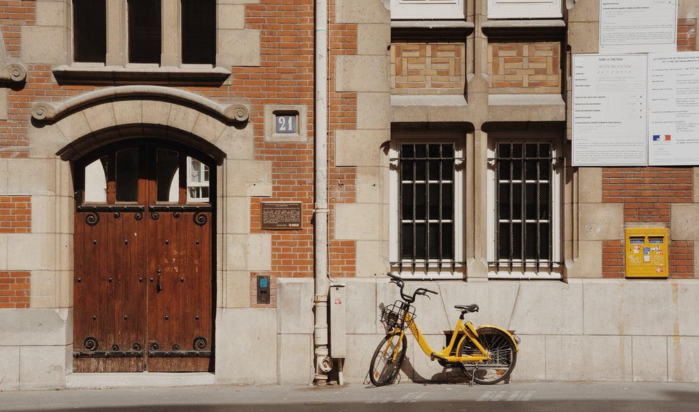 blue and yellow bicycles parked beside brown concrete building during daytime