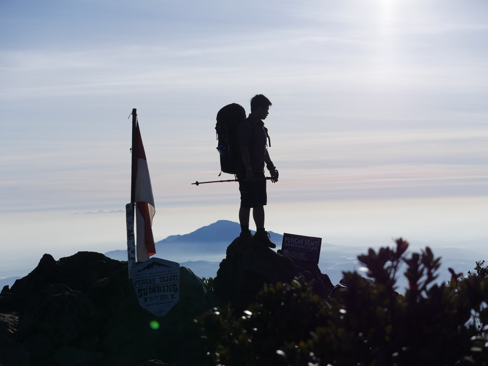 man and woman kissing on the top of the mountain during sunset