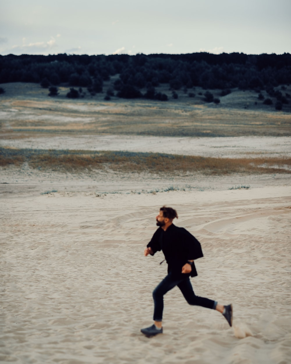 man in black shirt running on beach during daytime