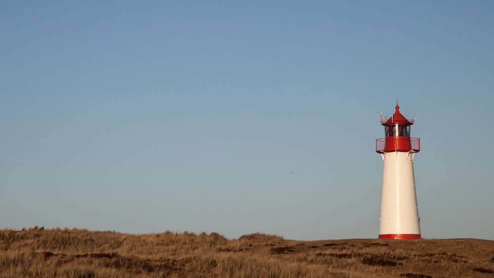 brown and white lighthouse on brown grass field under blue sky during daytime