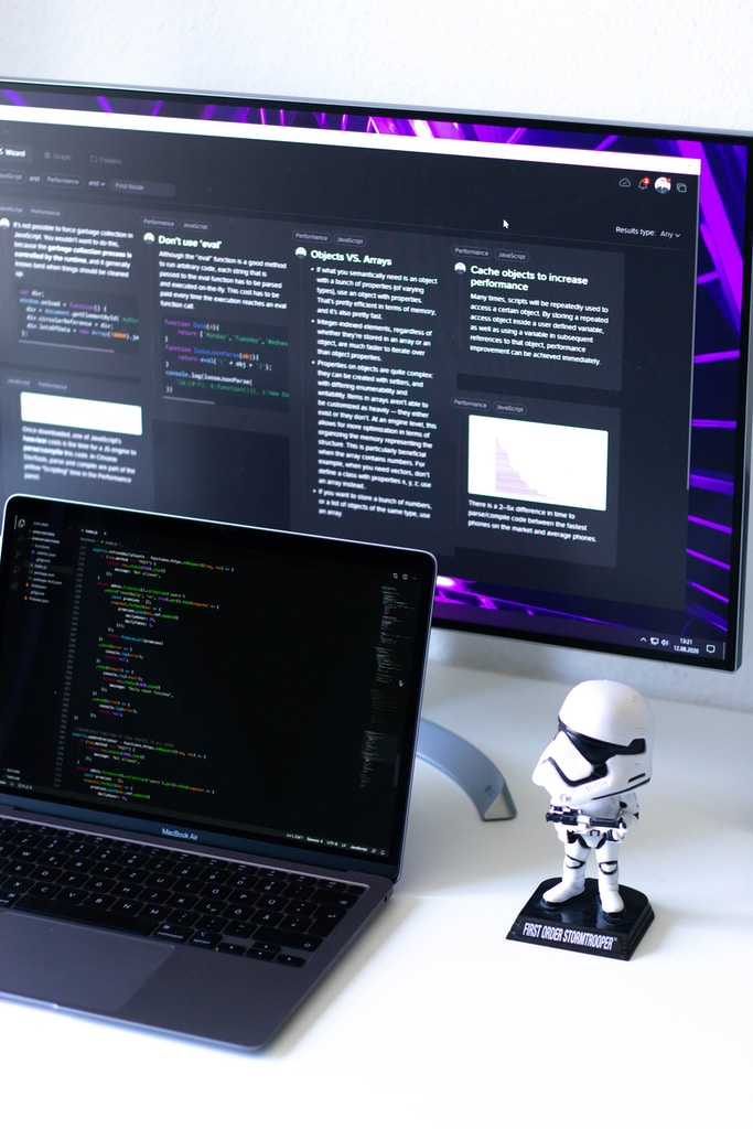 Beautiful and clean white desk with a purple desktop and a space-grey MacBook Air